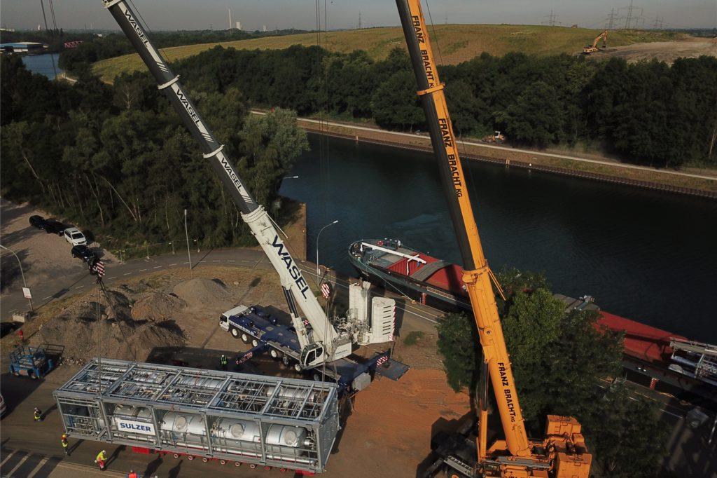 Zwei Autokrane heben die erste von zwei Teilanlagen von einem Kanalschiff auf einen Straßen-Schwertransporter.