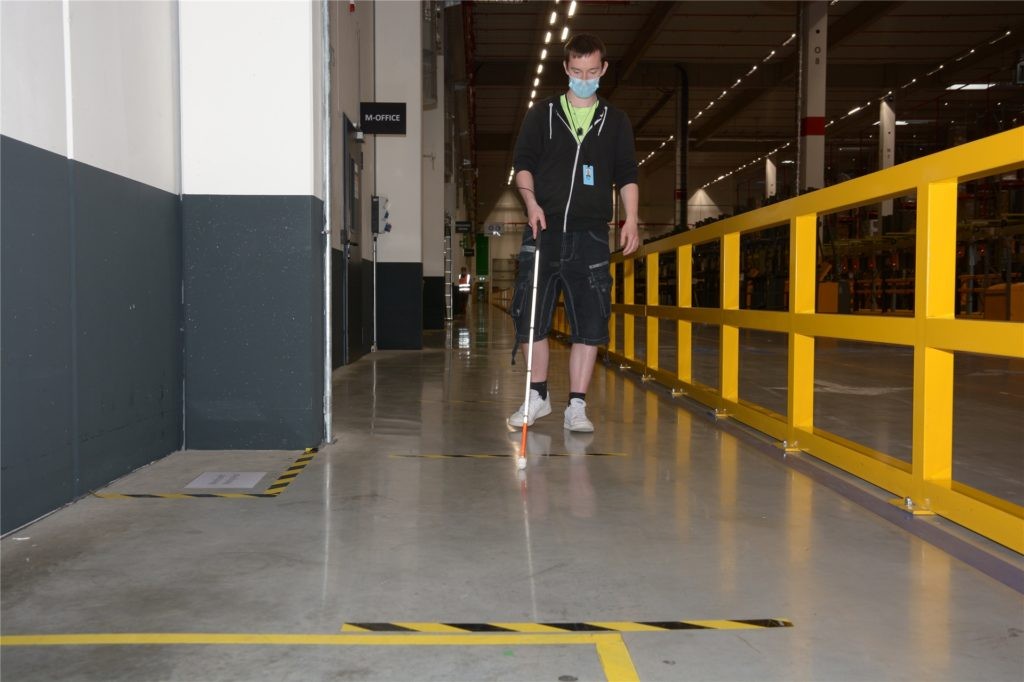 Was für viele Mitarbeiter schon ungewöhnlich ist, ist für Marvin Reher erst recht eine Herausforderung: Mit dem Blindenstock geht der 25-Jährige über die Markierungen, die an den Sicherheitsabstand erinnern.