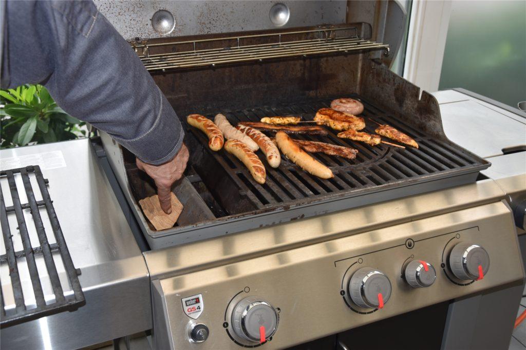 Wer mag kann beim Gasgrill einen Holzklotz auf die Brennstäbe legen. So erhält man ein rauchiges Aroma - wie man es auch vom Kohlegrill kennt.