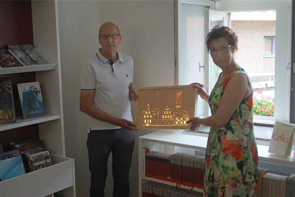 Herbert Aprill, Kassierer im Förderverein Stadtbücherei Werne, überreicht Gerlinde Schürkmann ein beleuchtetes Holzrelief mit den Sehenswürdigkeiten Wernes.