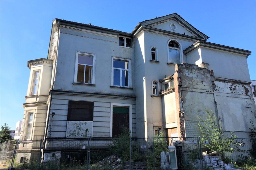 Auf der Rückseite sind Fenster zerstört, Tauben haben das Gebäude erobert.