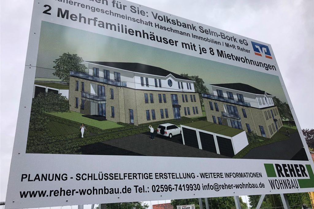 Das große Bauschild listet die Beteiligten auf und lässt ahnen, wie die Wohnhäuser einmal aussehen werden.