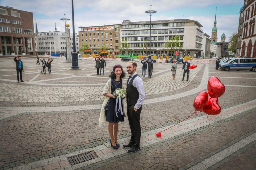 """Nur aus der Ferne konnten Freunde und Familie dem """"Corona-Brautpaar"""" nach der standesamtlichen Trauung gratulieren."""