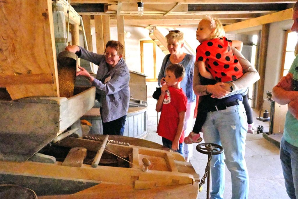 Beim Mühlentag: Maria Menke ist die Müllerin und demonstriert, wie die alte Mühlentechnik funktioniert.