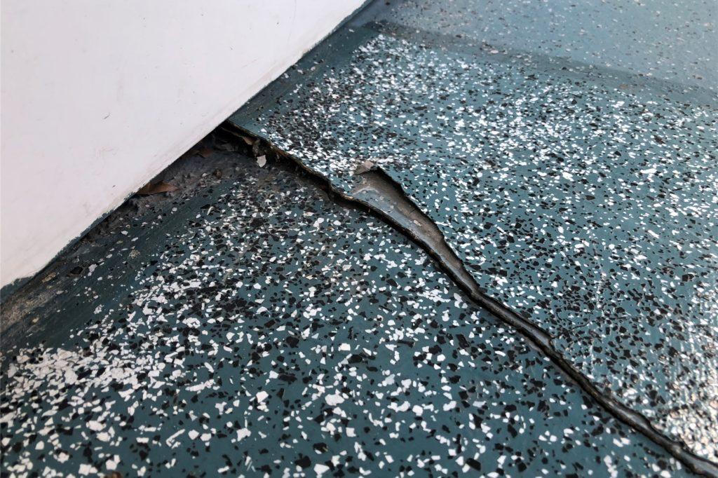 Ein Riss, der sich quer durch einen der Laubengänge zieht, wurde mit einer neuen Bodenplatte überklebt. Auch diese neue Platte reißt bereits wieder ein.