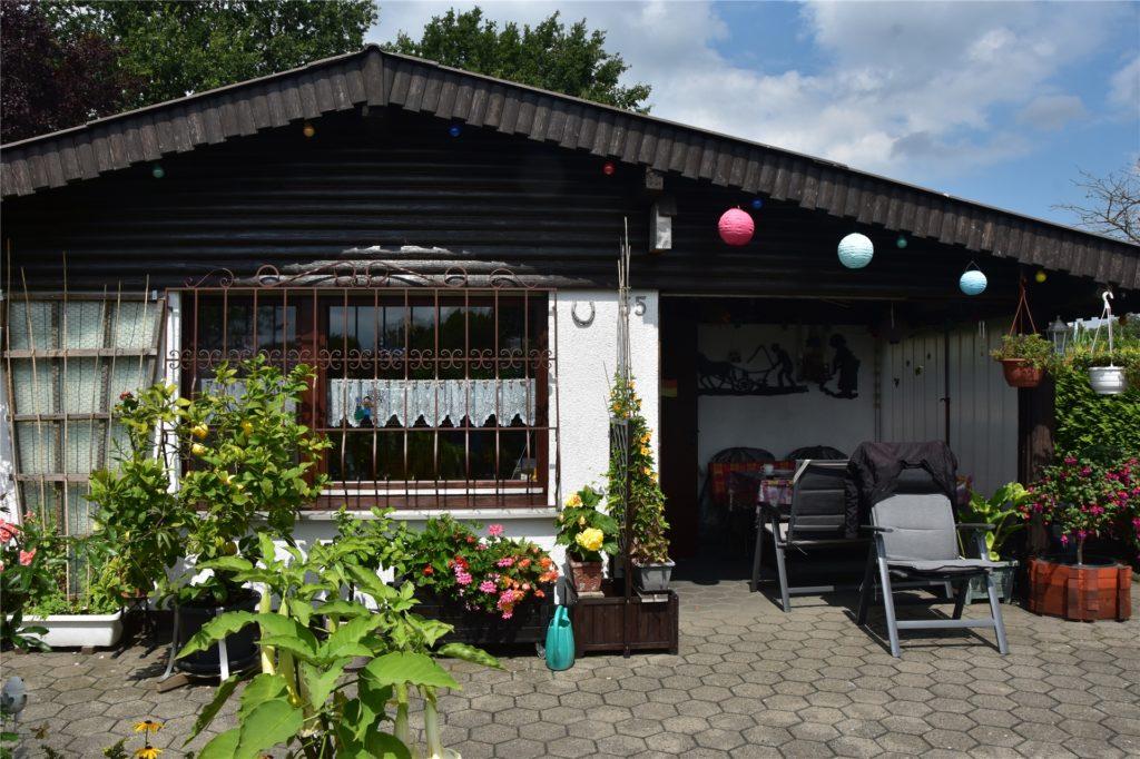 In dem Gartenhaus des Ehepaar Johns gibt es eine Küche, Toilette und Dusche. Links befindet sich eine Sitzecke.