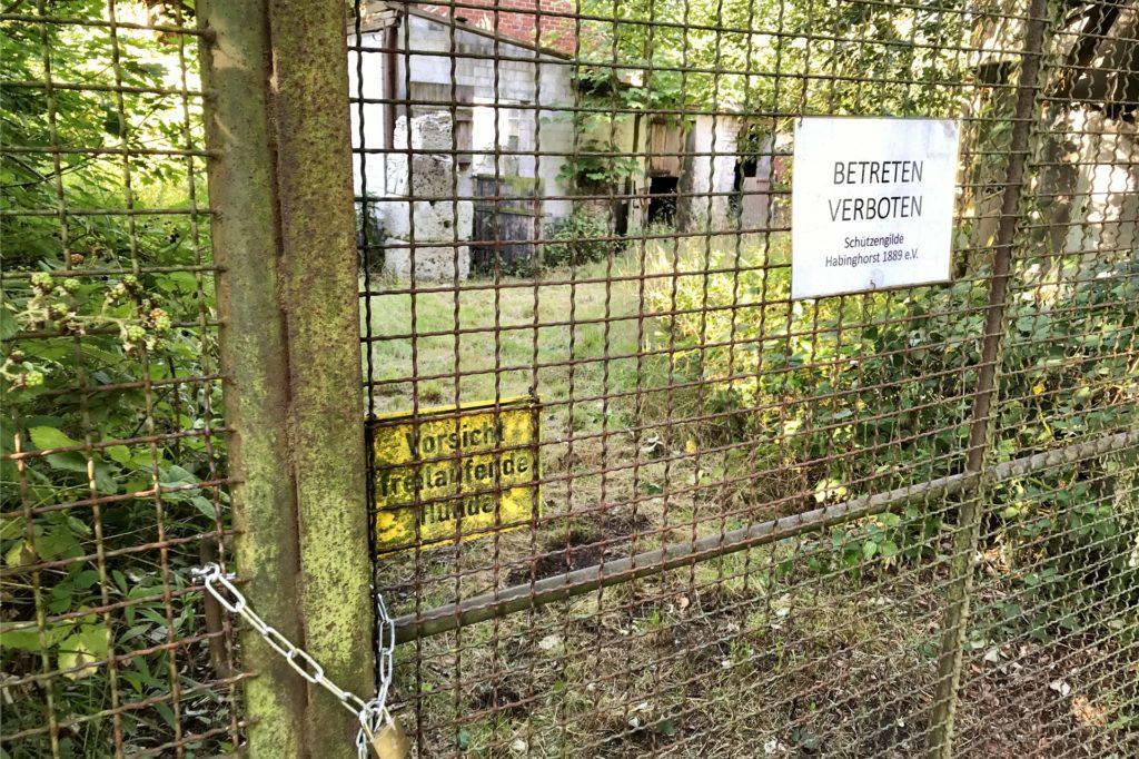 """Das Gelände ist mit Zäunen umgeben. Die Kette mit Schloss wirkt neu. Am Zaun warnt die Schüzengilde Habinghorst: """"Betreten verboten""""."""