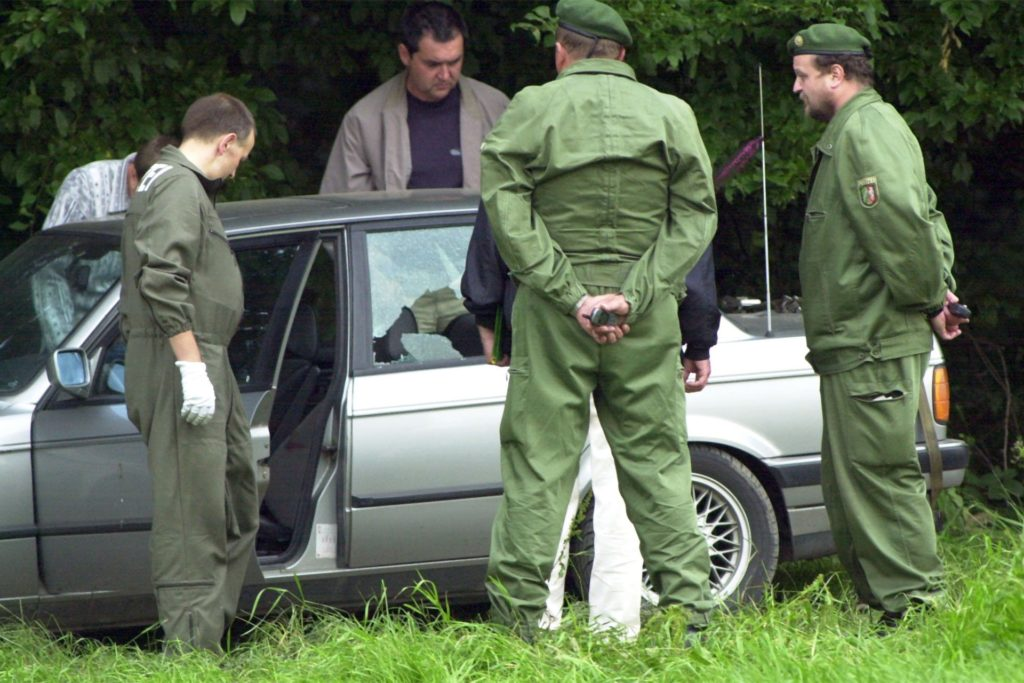 Polizisten am Fluchtfahrzeug (Archivbild aus dem Jahr 2000).