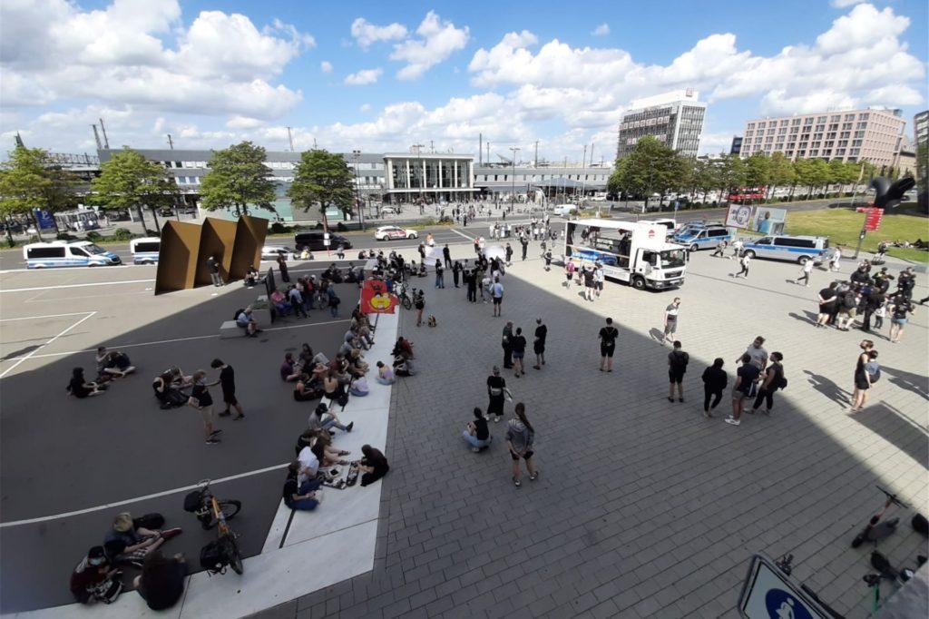 Demonstranten auf dem Platz vor dem Fußballmuseum, im Hintergrund ist der Hauptbahnhof zu sehen