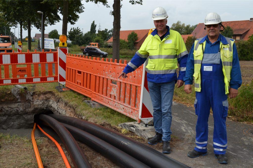Martin Enning (l.), Projektplaner bei Westnetz, und Andreas Gausling, Monteur im Netzbetrieb, zeigen die drei Leitungen, die in der Erde verlegt werden. Da die Leitungen unterirdisch gezogen werden, ist es nur an einigen Stellen nötig, die Erde aufzureißen.
