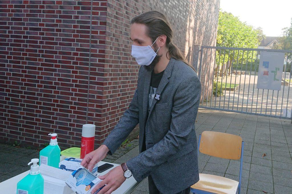 Julian Fuhrmann ist seit 2013 als Wahlhelfer aktiv. Bevor es an das Auszählen der Stimmen geht, kümmert er sich darum, dass die Wähler sich am Eingang die Hände desinfizieren und die Sicherheitsabstände einhalten.