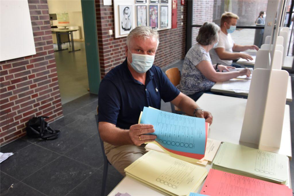 Wahlvorsteher Klaus Hüser teilt die Stimmzettel aus.