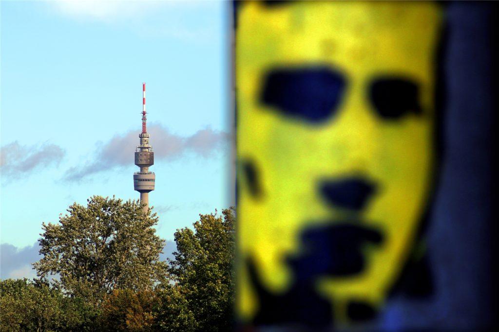 Dortmunder Stadtansicht: Im Vordergrund August Lenz auf einem Brückenpfeiler, im Hintergrund der Florianturm.