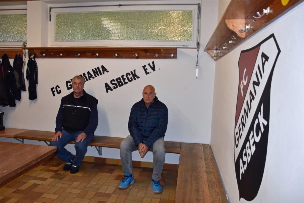 Ludger Wolter (l.) und Helmut Reckers (r.)  in der Umkleidekabine. Braun-orange Bodenfliesen, einfach-verglaste Fenster: Das Gebäude ist in die Jahre gekommen.