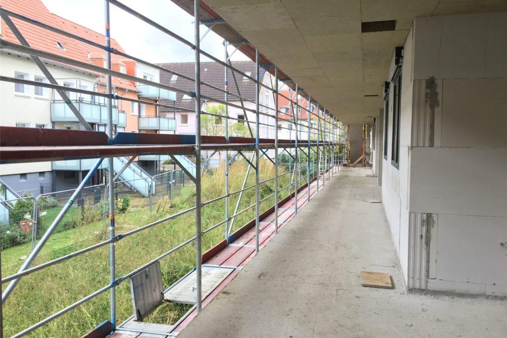 Die Wohnungen sind über Außenflure erreichbar. Links im Bild sind die benachbarten älteren Häuser zu sehen. Deren Bewohner zeigten sich über das Neubauprojekt vor ihrer Haustür teils wenig begeistert.