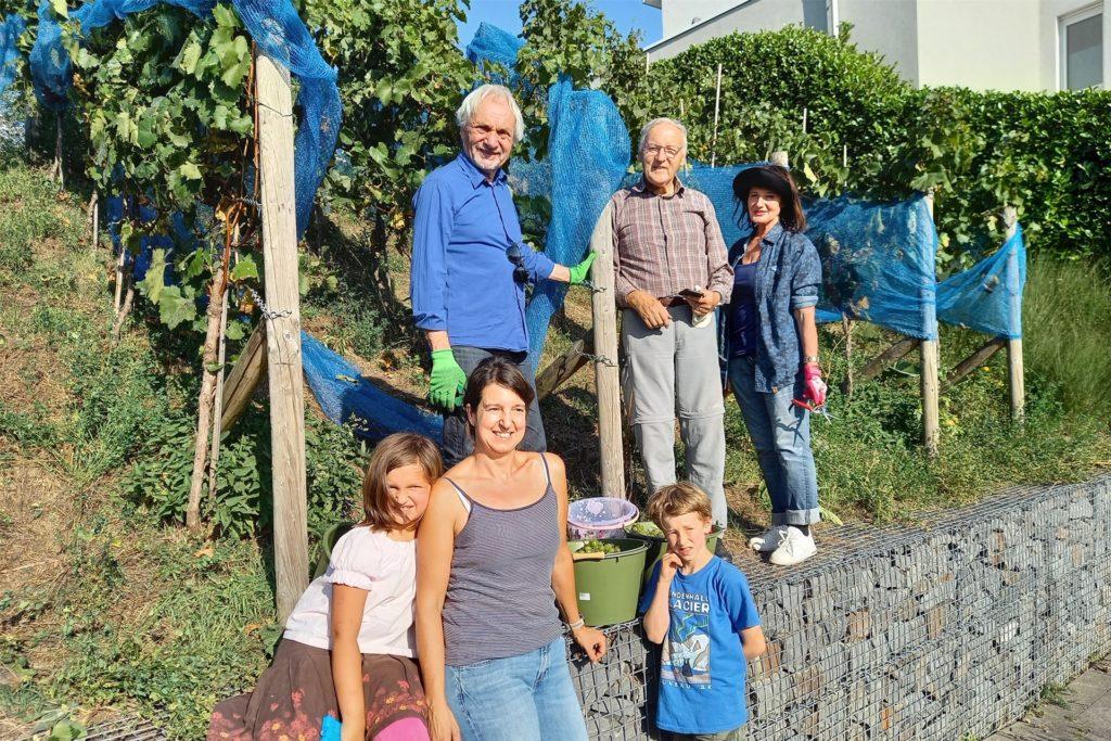 An der Weinlese 2020 beteiligten sich: (unten) Winzerin Tina Krachten mit Tochter Johanna und Gastkind Gustav sowie (oben) die seit der Pflanzung 2012 Aktiven Christoph Ebner, Willi Garth und Gabriele Ebner.