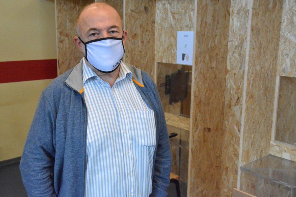 JVA-Leiter Ralf Bothge zeigt die hölzernen Kabinen, in denen die Besucher durch Scheiben von den Insassen abgetrennt sind.