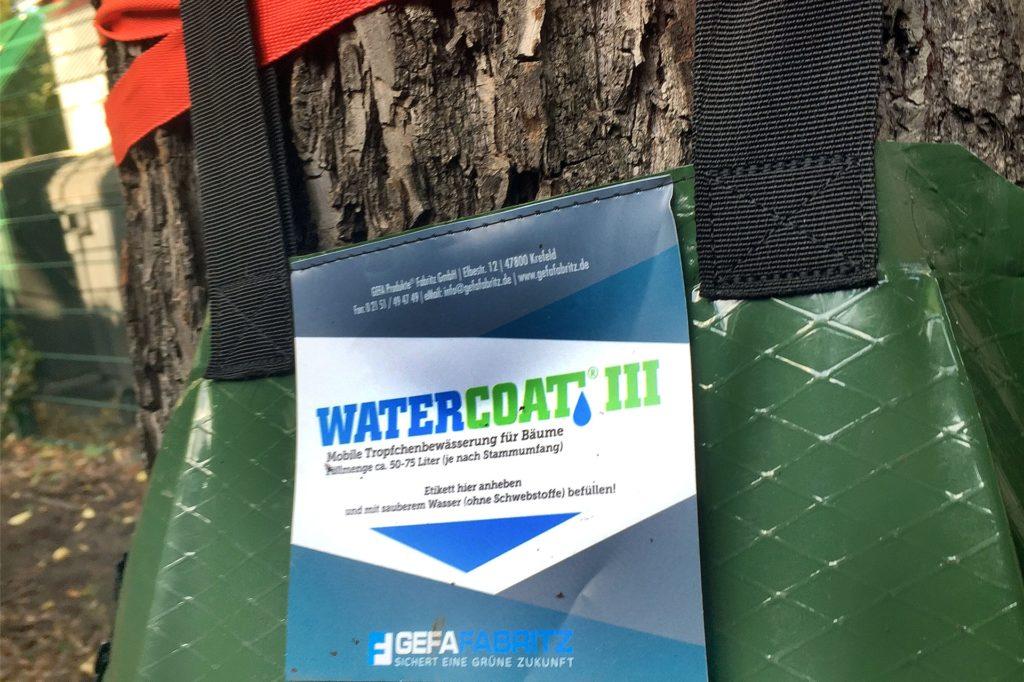 Ein Zettel über der Einfüllöffnung verrät: Die Kunststoffbeutel sind eine automatische Bewässerungsanlage für Bäume.