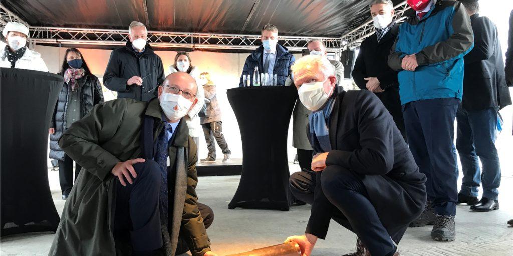 Bernd Kaffanke (l.) und Heinz-Werner Bitter freuen sich mit Bürgermeister Kravanja und anderen Gästen der kleinen Feierstunde auf dem Baugelände. In der Kapsel, die im Grundstein des Gesundheitscampus liegt, versenkten sie neben einer Zeitung auch eine Corona-Maske.