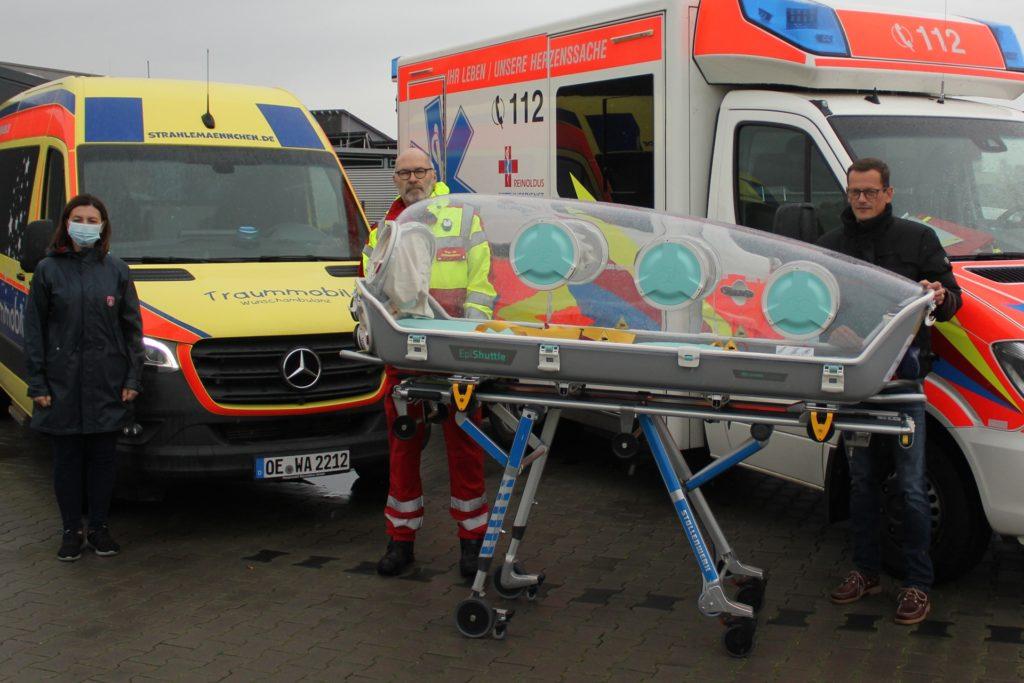 Joanna Junge (links), Rötger Dahm (mitte) und Peter Hill (rechts) vom Reinoldus Rettungsdienst steht seit vergangenem Wochenende eine Corona-Spezialtrage zur Verfügung.