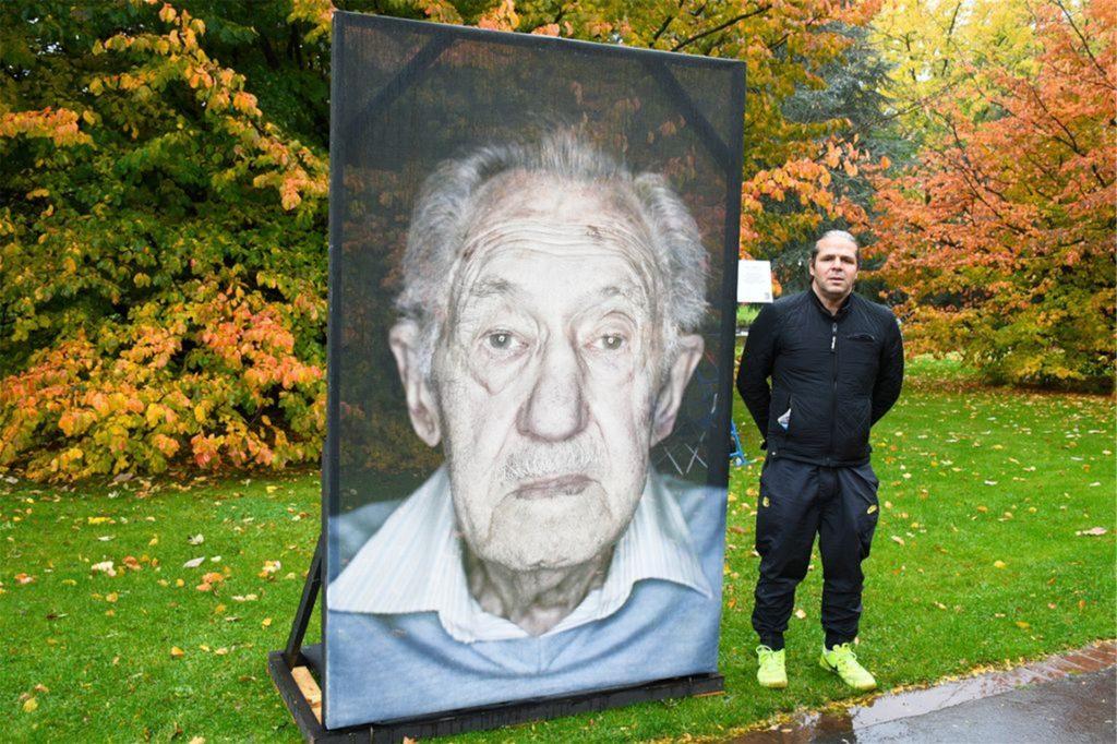 Der Fotograf Luigi Toscano vor dem Portrait des Auschwitzüberlebenden Horst Sommerfeld.