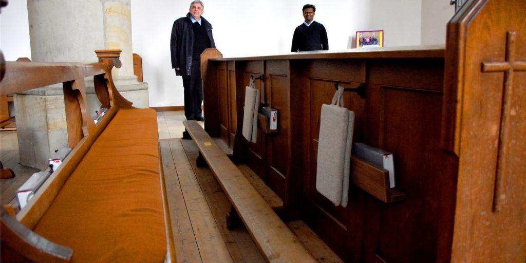 Pastor Stefan Scho (l.) und Pater Raju Peter an den Kirchenbänken in der Vituskirche.  Die Sitzplätze sind mit gelben Klebestreifen markiert. Seit der Kreis Borken wegen der hohen Coronainfektionszahlen Risikogebiet ist, müssen die Gottesdienstbesucher Mund-Nase-Schutz tragen.