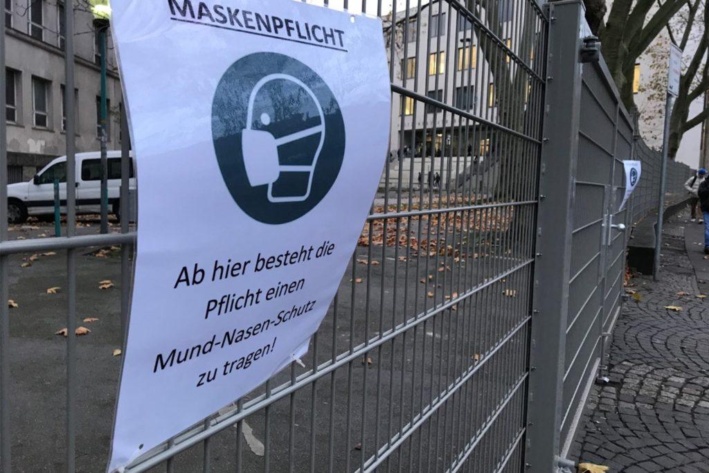 Am Zaun vor dem Hoesch- und dem Henßler-Berufskolleg hängt der deutliche Hinweis: Maske auf!