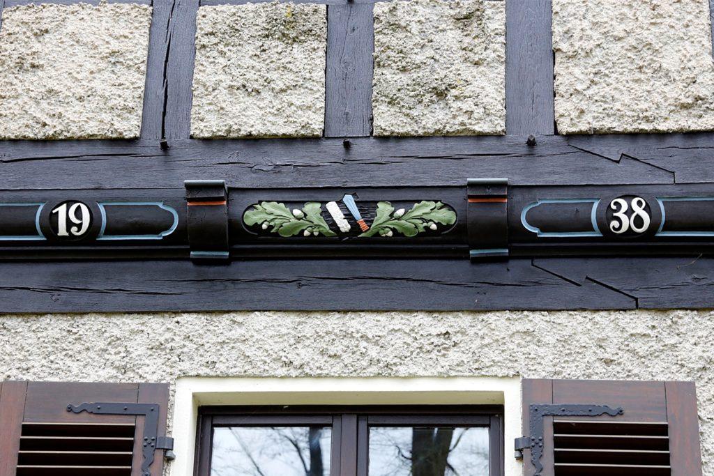 Ein Giebel trägt das Symbol des NS-Reichsnährstandes: Schwert und Ähre.