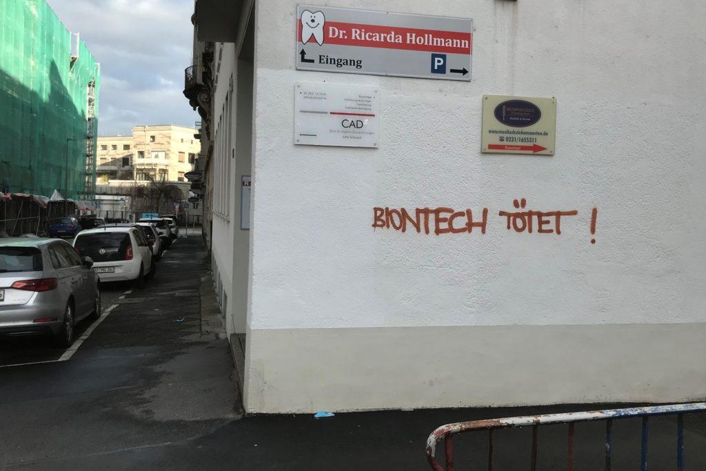 """An einer Hauswand an der Luisenstraße ist zu lesen: """"Biontech tötet""""."""