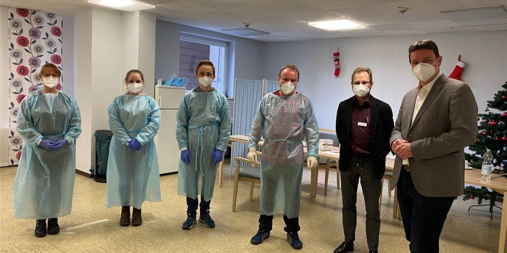 In Castrop-Rauxel haben die Impfungen gegen das Coronavirus begonnen. Heike Klosa (Arzthelferin), Senta Preissig (Auszubildende), Marius Preissig (Praktikant), Dr. Anton Preissig (Arzt) und Mathias Müller (Einrichtungsleitung des Kauermann-Seniorenzentrums) freuen sich mit Bürgermeister Kravanja, dass es nun mit dem Impfen losgehen kann.