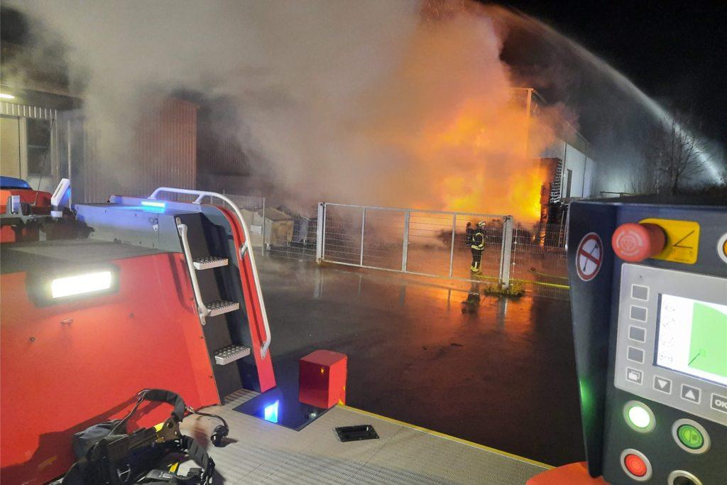 Der Einsatzort lag hinter einem Hallenkomplex, angrenzend an einem Waldstück. Aus unbekannter Ursache brannten Müllcontainer und gestapelte Paletten an einem Hallenkomplex.