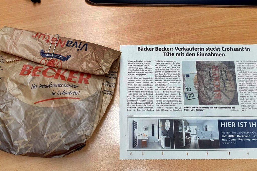 Als sie in den Ruhr Nachrichten von dem verhängnisvollen Irrtum der Verkäuferin gelesen hatte, machte sich Michaela Kops auf die Suche nach der Brötchentüte mit dem Geld. Zeitung und Originaltüte fotografierte sie dann vor der Rückgabe auf ihrem Schreibtisch.