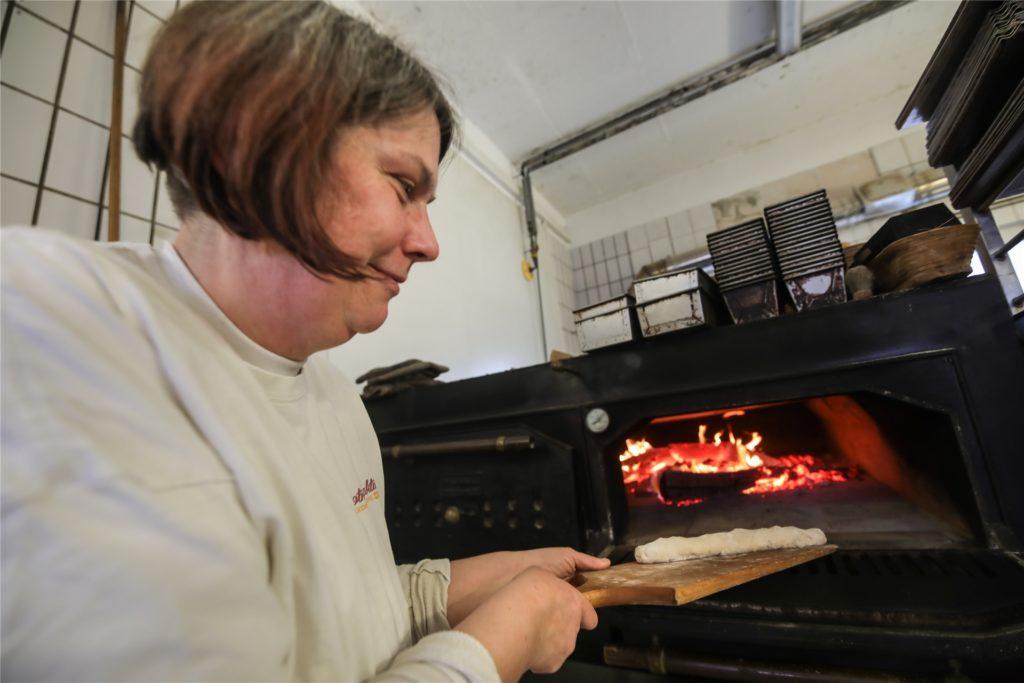 Fünf Stunden wird der Ofen mit Buchenholz angeheizt, bevor Bäckermeisterin Denise Sippel die Brote zum Backen hineinschieben kann.