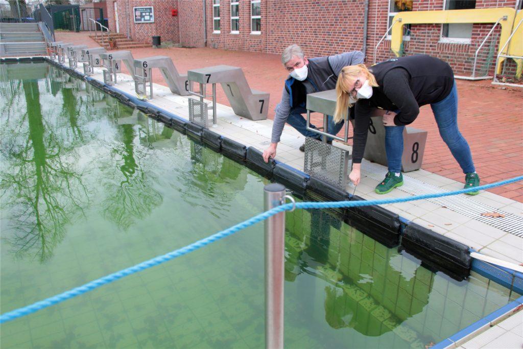 Marco Dellwig und Barbara Kipp an dem gefüllten Außenbecken des Solebads mit Eisdruckpollern, die bei Frost Beschädigungen verhindern sollen.
