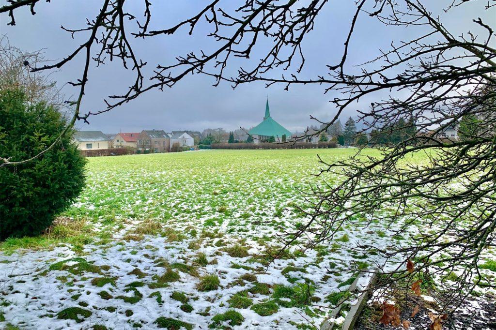 Wo jetzt noch Gras wächst, wachsen bald Häuser. Im Hintergrund ist die Katholische Kirche auf dem Höchsten.