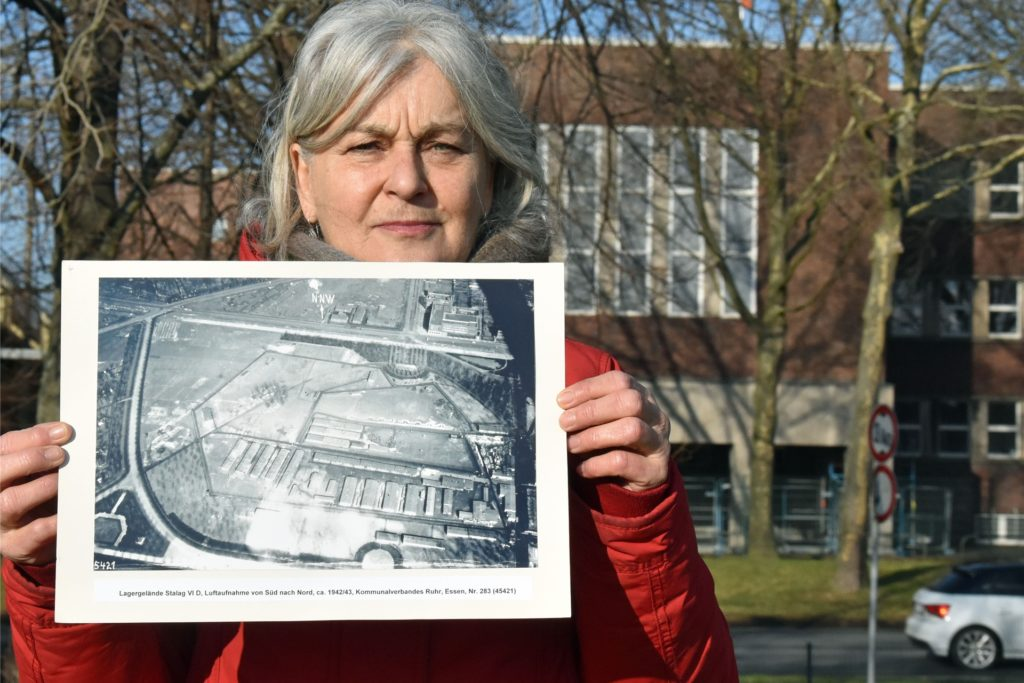 Die Historikerin hält eine Luftbildaufnahme des Geländes von 1942/43 in den Händen. Die Baracken sind deutlich zu erkennen.