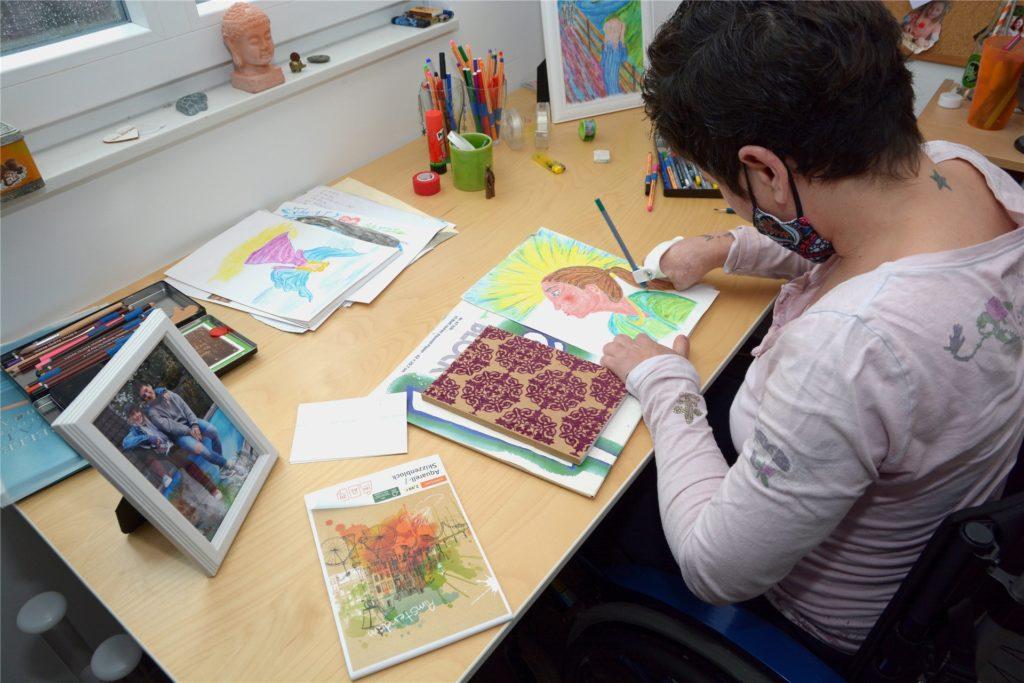 Curbach (43) malt gerne - auch wenn sie nur noch einen einzigen Finger hat. Eine Schreibhilfe ermöglicht es ihr, kleine Kunstwerke zu erschaffen.