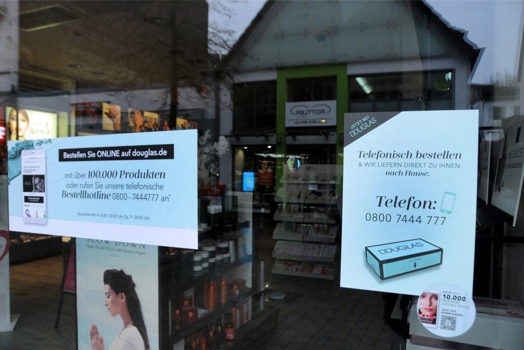 Plakate im Schaufenster der Douglas-Filiale an der Hüsingstraße werben für die telefonische Bestellung.