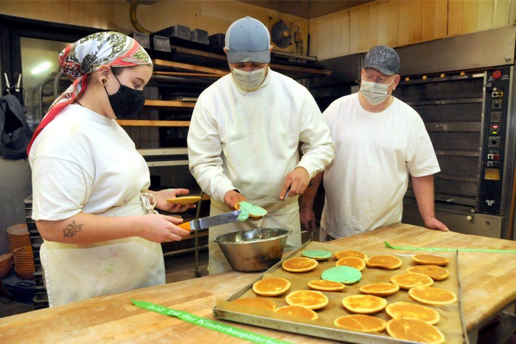 In der Backstube von Bäcker Becker glasieren Bäckermeister Sascha Ruhnke (M.) und sein Team die grünen Amerikaner, deren Verkaufserlös zur Hälfte an den Ambulanten Kinderhospizdienst Unna gespendet wird.