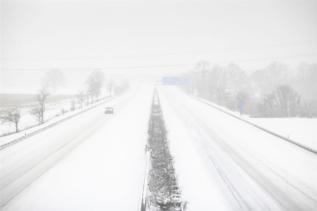 Ein Auto fährt über die völlig zugeschneite Autobahn 2.