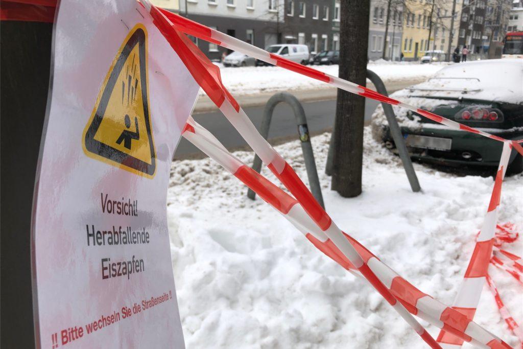 Ein Schild weist auf herabfallende Eiszapfen hin und fordert auf, die Straßenseite zu wechseln.