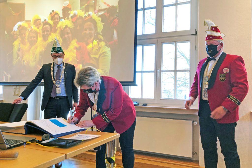 Prinzessin Susanne Hornhues und Prinz Manfred Schwenz tragen sich ins Goldene Buch der Stadt Stadtlohn ein; links Bürgermeister Berthold Dittmann.