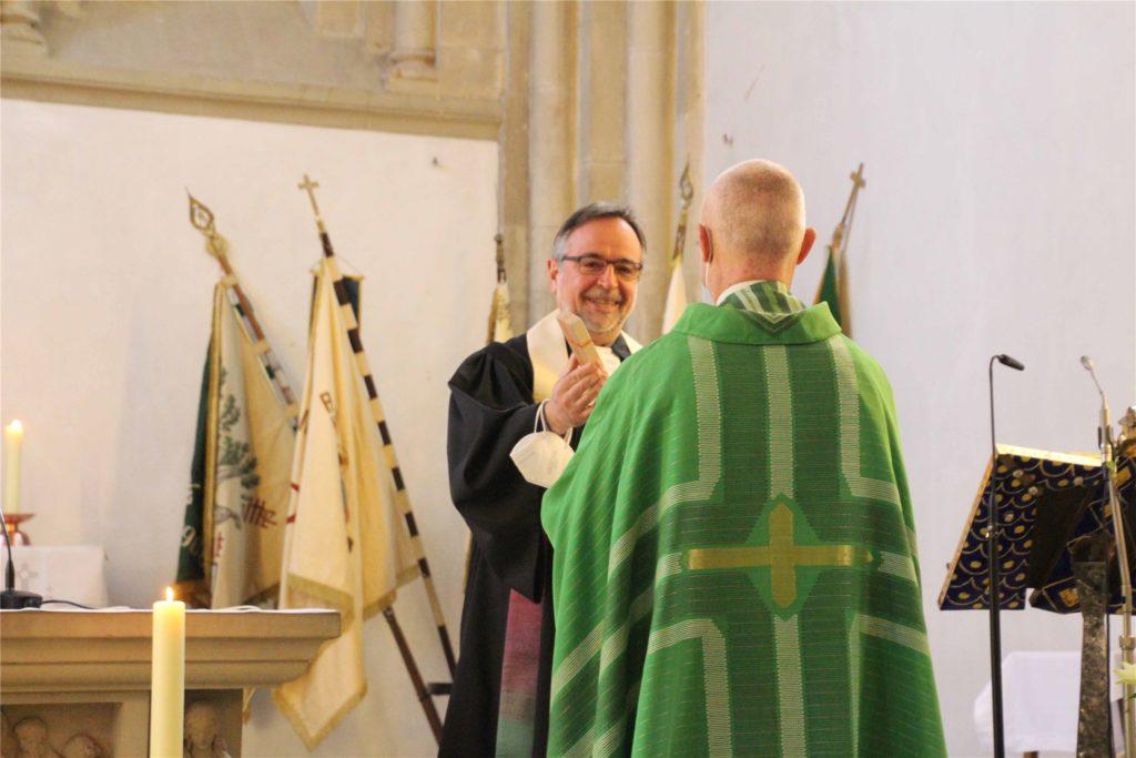 Der evangelische Pfarrer Olaf Goos (l.) überreicht das Lichtkreuz an seinen katholischen Amtsbruder Siegfried Thesing (r.)