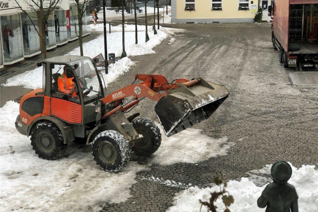 Mitarbeiter des Baubetriebshofes räumen am Montag (15. Februar) Schnee vom Marktplatz, damit weitere Händler ihre Stände auf dem Wochenmarkt aufbauen können.