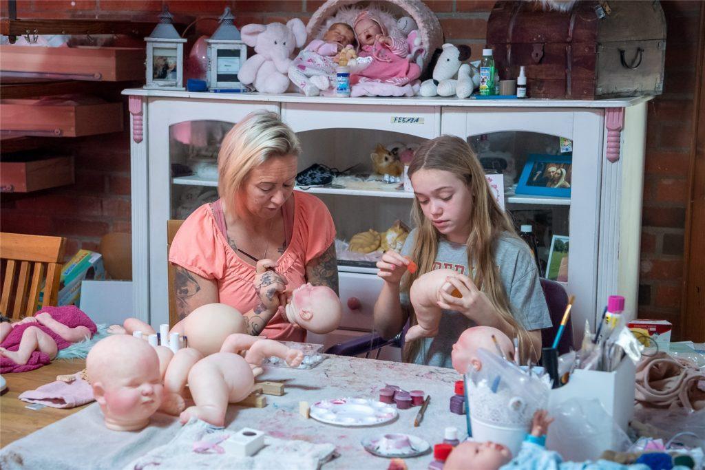 Jasmin Karl und ihre Tochter Finja bemalen täuschend echt aussehende Puppen.