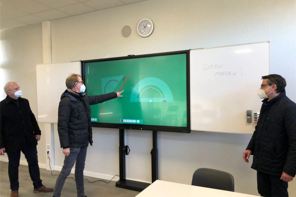 Schulleiter Jochen Wilsmann (M.) zeigt Bürgermeister Berthold Dittmann (r.) und dem Ersten Beigeordneten Günter Wewers die Möglichkeiten der neuen digitalen Touchscreentafel.