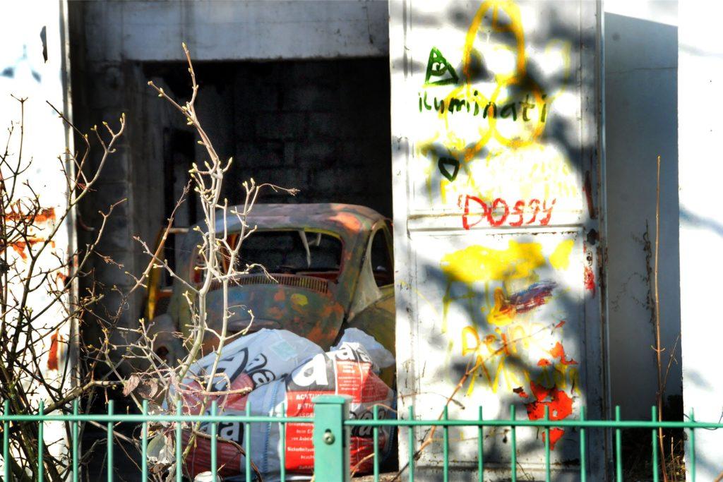 Das Wrack eines VW-Käfers ist hinter den offenstehenden Toren der ehemaligen Klempnerei zu erkennen.