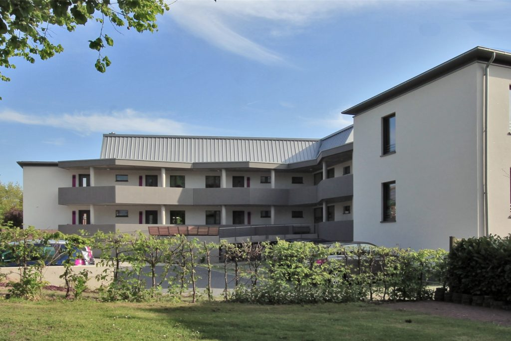 Die Ansicht des Genossenschaftshauses zur Straßenseite: Laubengänge verbinden die Wohnungen.