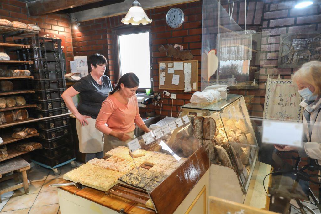 In der gemütlichen Bäckerei stapeln sich die Brote im Holzregal und in der Theke.