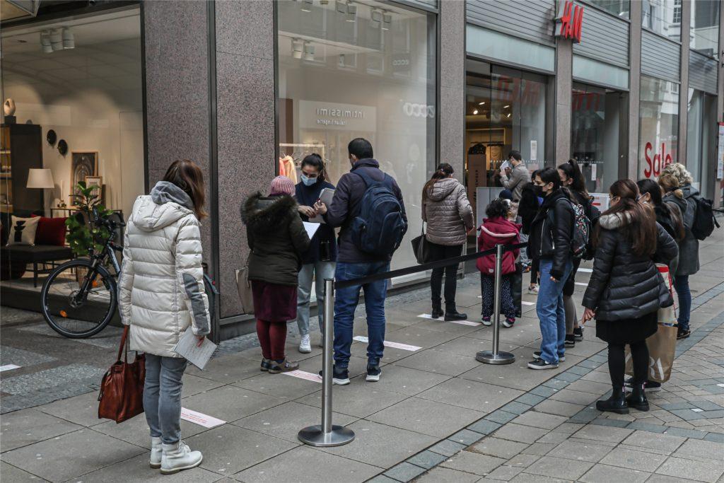 Vor H & M erklärt eine Mitarbeiterin Kunden, wie sie das Papierformular ausfüllen müssen.